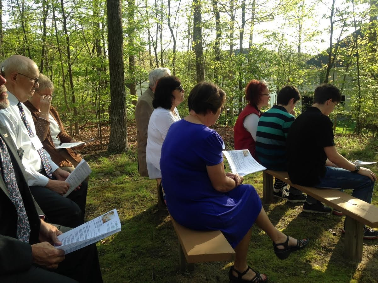 people sit on benches in the woods at the gayton kirk presbyterian church for outdoor celtic worship service