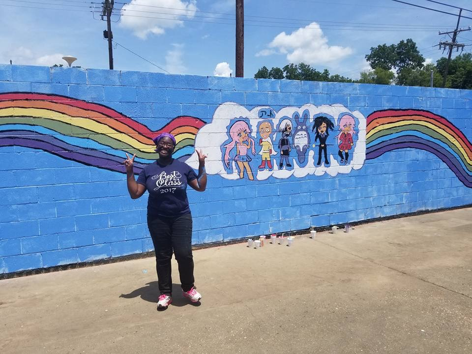girl standing in front of rainbow mural as part of The Gayton Kirk progressive Christian missions in Richmond VA