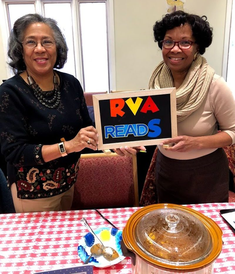 Two women hold the RVA Reads sign at a Chili Cookoff at the Gayton Kirk Presbyterian Church in Richmond VA